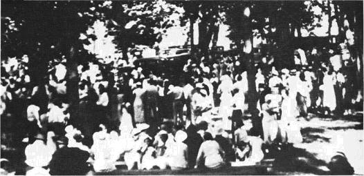 Settlers sitting under trees, having a picnic
