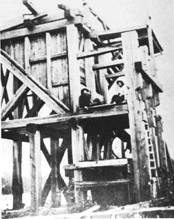 Men sitting on structure over Little American Mine