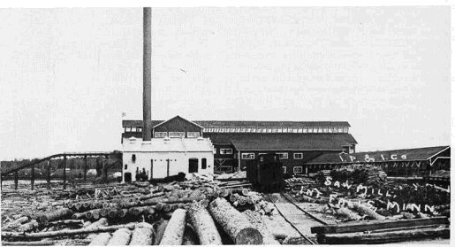 Logs outside International Lumber Sawmill building in 1911